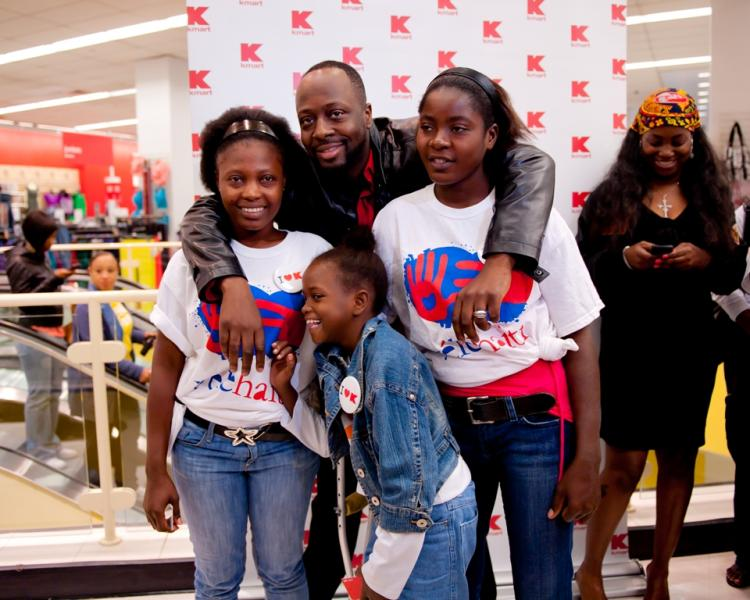 Wyclef poses with amputees Margarette, on the right, Chantal on the left and little Farah in the front as they pose for a few pictures before setting off on a shopping spree at Penn Station KMart on Tuesday.  (Aloysio Santos/The Epoch Times)