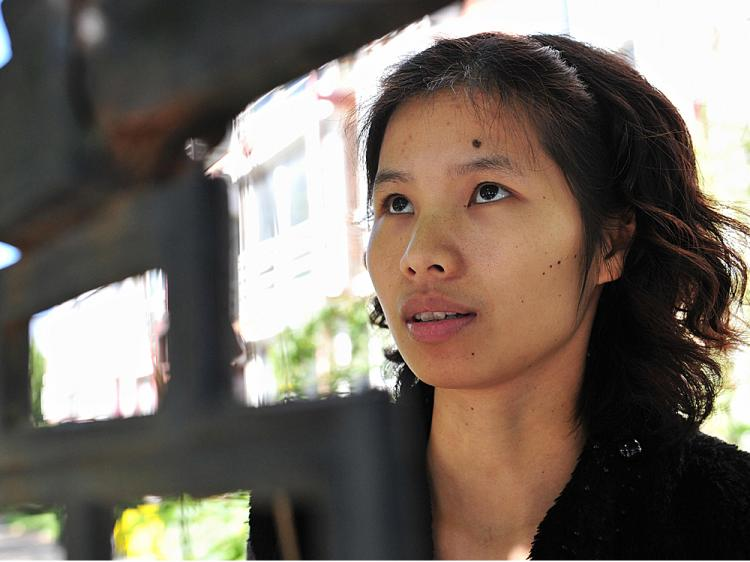 Chinese dissident Zeng Jinyan stands behind a gated compound at Bobo Freedom Village where she lives under unofficial house arrest   (Frederic J. Brown/AFP/Getty Images)