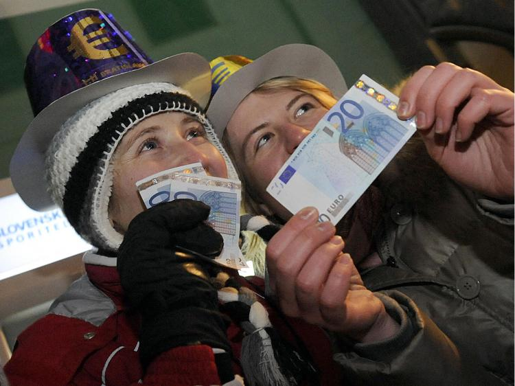 People celebrate after collecting their first twenty euros from a cash machine in the centre of Bratislava's main square on January 1,2009, after Slovakia joined the eurozone.    (Samuel Kubani/AFP/Getty Images)