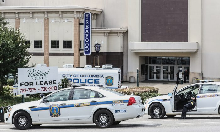 Columbia Police Officers investigate the scene where a Forest Acres Police Officer was fatally shot in the Richland Mall Wednesday, Sept. 30, 2015, in Forest Acres, S.C. Police say a suspect is in custody.  (Matt Walsh/The State via AP)
