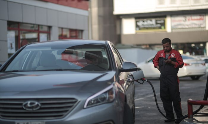 In this Wednesday, Sept. 16, 2015, photo, a car fills up at a gas station in Jiddah, Saudi Arabia. (AP Photo/Mosa'ab Elshamy)