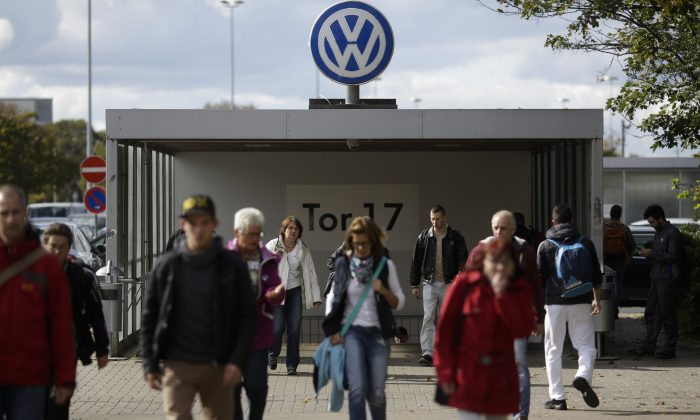 In this photo taken on Sept. 29, 2015 people leave Volkswagen factory at Gate 17 in the city Wolfsburg, Germany. (AP Photo/Markus Schreiber)
