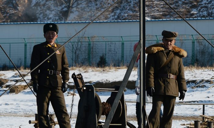 North Korean soldiers stand guard beside a barge used to ferry goods and people across to a North Korean island near the Chinese border town of Dandong on December 15, 2013. (Photo credit should read MARK RALSTON/AFP/Getty Images)