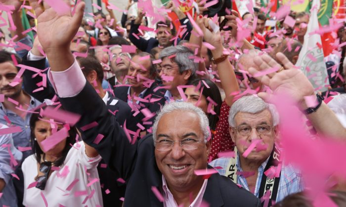 Antonio Costa, leader of the Portuguese Socialist Party, waves while being showered with confetti during an election campaign march through downtown Lisbon, Friday, Oct. 2 2015. (AP Photo/Armando Franca)