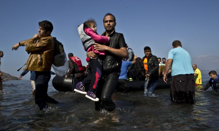A Syrian refugee man carrying his daughter rushes to the beach as he arrives on a dinghy from the Turkish coast to the northeastern Greek island of Lesbos, Sunday, Oct. 4 , 2015.  (AP Photo/Muhammed Muheisen)