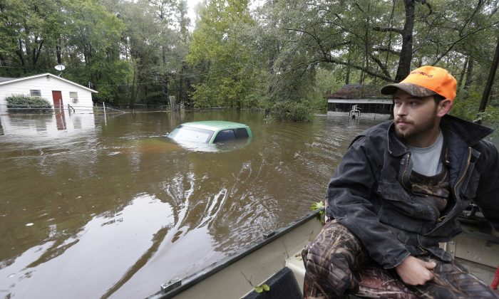 Hunter Baker surveys flood damage to his neighborhood near the flooded Black Creek following heavy rains in Florence, S.C., Monday, Oct. 5, 2015.  (AP Photo/Gerry Broome)