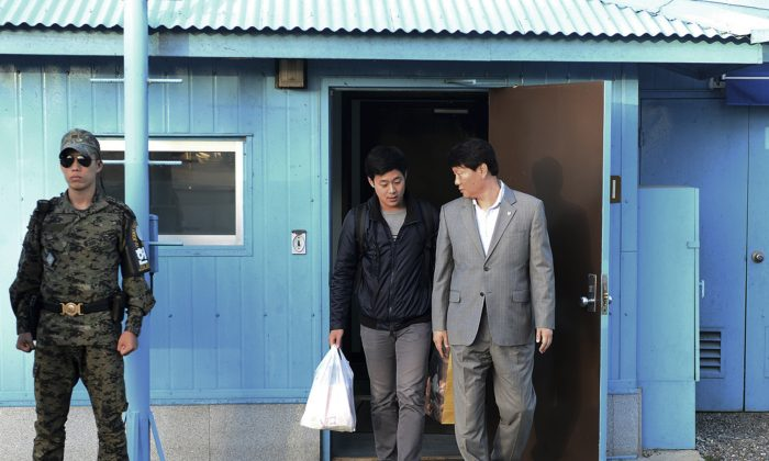 In this photo provided by the South Korean Unification Ministry, South Korean Won Moon Joo, center, who has a permanent resident status in the United States, is escorted by a South Korean official at the border village of Panmunjom in Paju, South Korea, Monday, Oct. 5, 2015. (The South Korean Unification Ministry via AP)