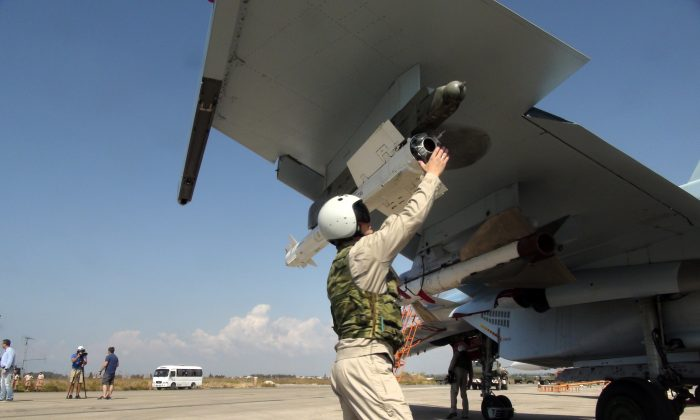 Russian pilot fixes an air-to-air missile at his Su-30 jet fighter before a take off at Hmeimim airbase in Syria, on Monday, Oct. 5, 2015. (AP Photo/Dmitry Steshin, Komsomolskaya Pravda, Photo via AP)