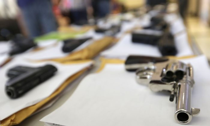 Chicago police display some of the thousands of illegal firearms they have confiscated so far this year in their battle against gun violence in Chicago on July 7, 2014. (AP Photo/M. Spencer Green)