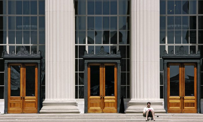 A doctoral student at the Massachusetts Institute of Technology reads outside a building at the Cambridge, Mass. campus, on April 22, 2007. (AP Photo/Michael Dwyer, File)