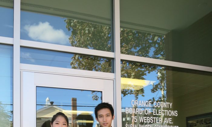 Ashley Wei (L) and Andrew Fung hold up their U.S. passports outside the Orange County Board of Elections office in Goshen on Oct. 6, 2015. Both Wei and Fung were there to clear the record after the Board incorrectly canceled their voter registration over questions of their residency.
