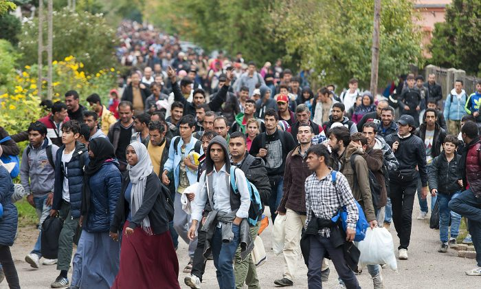 Migrants walk along a street after they arrived by train in Hegyeshalom, at the Austrian border, 169 km west of Budapest, Hungary, Wednesday, Oct. 7, 2015. (Csaba Krizsan/MTI via AP)