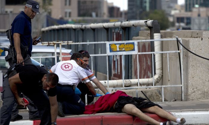 CORRECTS FROM WOUNDED TO DEAD -   Israeli medics check a dead Palestinian man after he stabbed a few Israelis in an attack in Tel Aviv, Israel, Thursday, Oct. 8, 2015. Israeli police says a soldier shot and killed an Arab attacker after he stabbed four people with a screwdriver in Tel Aviv. (AP Photo/Oded Balilty)