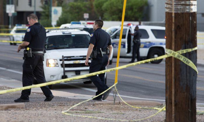 Phoenix police officers arrive at the scene where a Phoenix police officer was shot early Wednesday, Sept. 16, 2015 in Phoenix, Ariz. (Emmanuel Lozano/The Arizona Republic via AP)