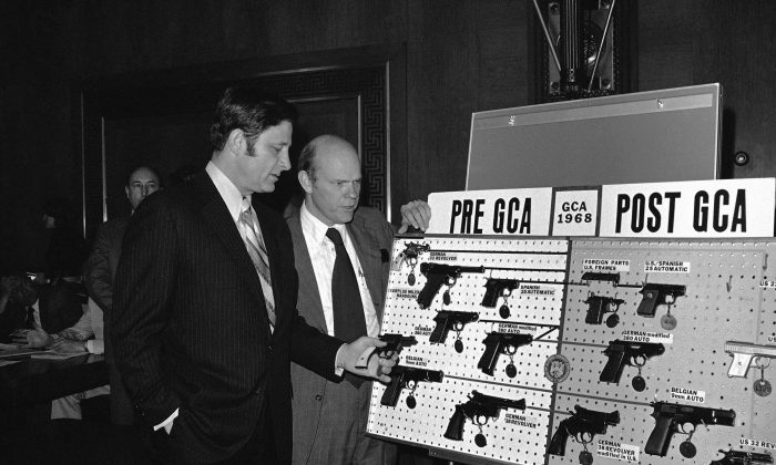 "FILE - In this Wednesday, April 23, 1975 file photo, Sen. Birch Bayh, D-Ind., left, chairman of the Senate judiciary subcommittee on juvenile delinquency, and David MacDonald, assistant secretary of treasury, look over a display of guns prior to hearings on gun control in Washington. Republican President Richard Nixon also favored gun control. Bayh says that the NRA helped prevent his 1972 bill banning ""Saturday night special"" handguns from getting through Congress. (AP Photo/Henry Griffin)"