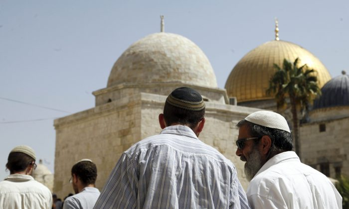 A group of religious Jews walk in front of the Dome of the Rock in Jerusalem on July 28, 2015. (AP Photo/Mahmoud Illean)
