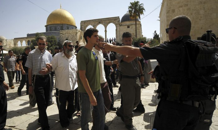 This Thursday, July 28, 2015 photo shows a group of religious Jews escorted by Israeli police at Al-Aqsa compound in Jerusalem.  (AP Photo/Mahmoud Illean)