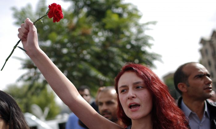 A woman participates at a memorial service for the victims of Saturday's attacks , at the site of the bombings in Ankara, Turkey, Monday, Oct. 12, 2015. (AP Photo/Emrah Gurel)