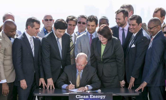 In this Oct. 7, 2015, file photo, California Gov. Jerry Brown, sitting center, surrounded by government officials, signs landmark legislation by Senate President pro Tempore Kevin De Leon, third from left, to combat climate change at a ceremony at the Griffith Observatory in Los Angeles. (AP Photo/Damian Dovarganes)
