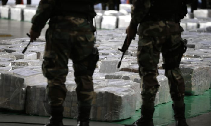 In this Sept. 1, 2014, file photo, police officers stand guard over seized cocaine they present to the press in Lima, Peru. (AP Photo/Martin Mejia)