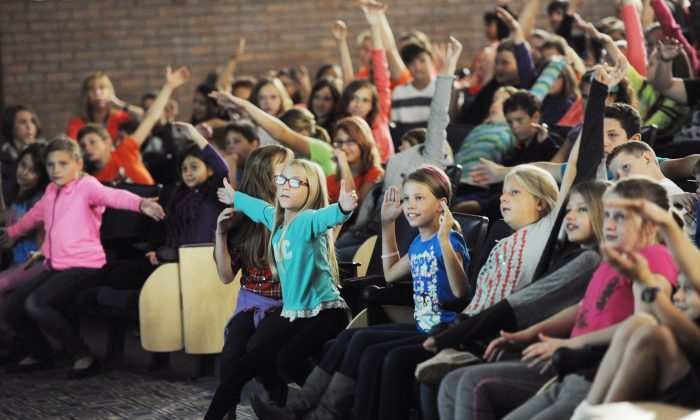 Middle school students respond to former American Idol contestant Devyn Rush as she talks about the pain bullying can cause during a bullying prevention assembly at Bridgman High School, in Bridgman, Mich., on Oct. 7, 2015. (Don Campbell/The Herald-Palladium via AP)