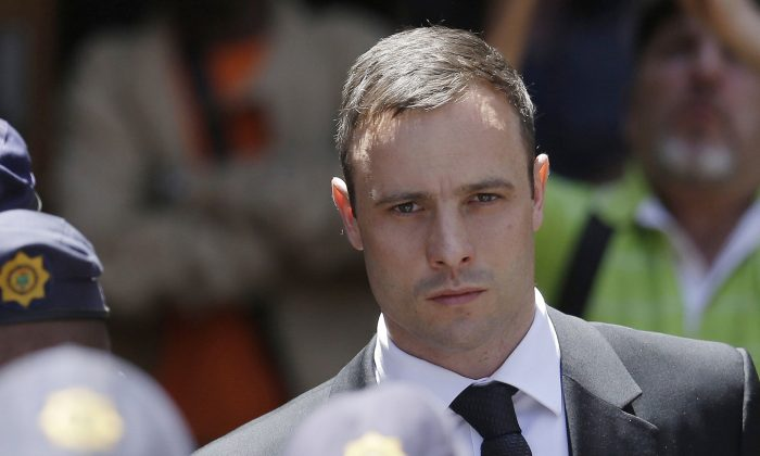 Oscar Pistorius is escorted by police officers as he leaves the high court in Pretoria, South Africa, on Oct. 17, 2014. (AP Photo/Themba Hadebe)