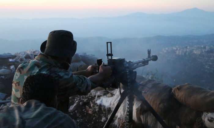 Syrian army personnel fire a machine gun in Latakia Province, Syria, about 12 miles from the border with Turkey, on Oct. 10, 2015. (Alexander Kots/Komsomolskaya Pravda via AP)