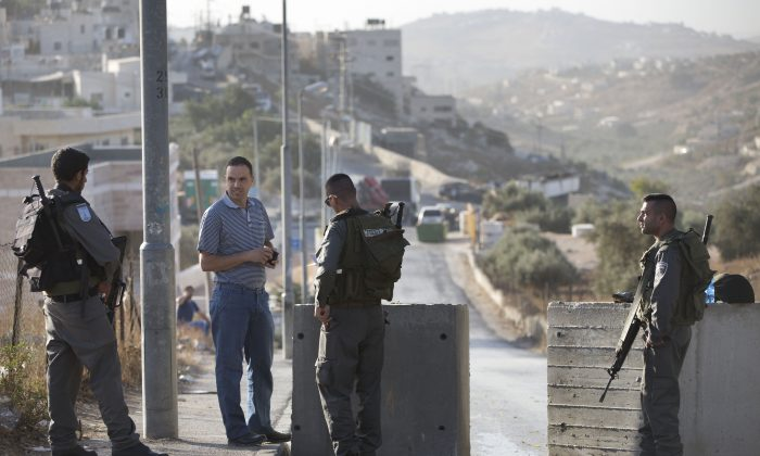 Israeli border police check Palestinian man ID next to newly placed concrete blocks in east Jerusalem neighborhood, Thursday, Oct. 15, 2015. (AP Photo/Oded Balilty)