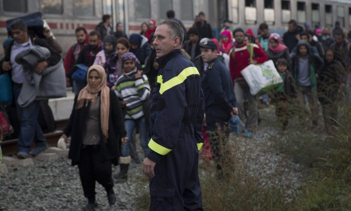 People disembark from a train in Botovo, on the Croatia-Hungary border, Friday, Oct. 16, 2015. Hungary clamped down on its border with Serbia with a barrier on Sept. 15 and says it will close down its border with Croatia to migrants starting at midnight. More than 383,000 migrants have entered Hungary this year, nearly all passing through on their way to Germany and other destinations farther west in the EU. (AP Photo/Darko Bandic)