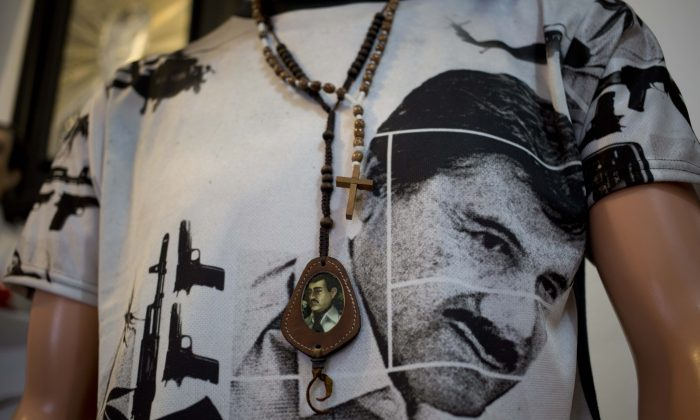"""A T-shirt of fugitive Mexican drug lord Joaquin """"El Chapo"""" Guzman covers a mannequin representing Jesus Malverde, known in Mexico as the """"saint"""" of drug traffickers, inside the shrine of a faith healer in Mexico City, on Oct. 16, 2015. The government is offering a reward of 60 million pesos (about $3.5 million) for Guzman's recapture after he made his second escape from a maximum security prison through an underground tunnel in 2015. (AP Photo/Eduardo Verdugo)"""