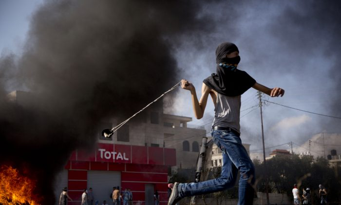 A Palestinian hurls a stone during clashes with Israeli troops near Ramallah, West Bank, on Oct. 14, 2015. Violence quickly spread across Israel and into the West Bank and Gaza Strip after clashes erupted last month over tensions regarding the Al-Aqsa Mosque compound in Jerusalem's Old City. (AP Photo/Majdi Mohammed)