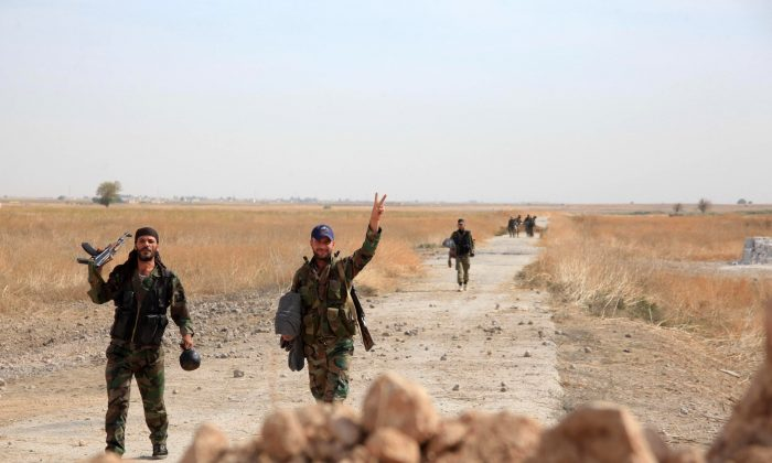 Syrian regime soldiers gesture as they walk down a road in an area around Kweyris military airport, in the eastern Aleppo Province, on Oct. 18, 2015. (George Ourfalian/AFP/Getty Images)
