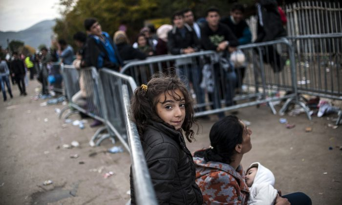 A young girl stands smiles from behind a barrier as migrants and refugees wait to be registered at a refugee center in Presevo, southern Serbia, on October 19, 2015. (ARMEND NIMANI/AFP/Getty Images)