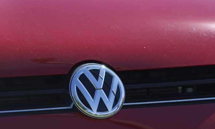 The grille of a Volkswagen is decorated with the iconic company logo on the lot of a VW dealership in Boulder, Colo., on Sept. 24, 2015. Shares in automaker Volkswagen are sliding after U.S. environmental officials said the company equipped more models than previously thought with software that let the cars cheat on diesel emissions tests. (AP Photo/Brennan Linsley)