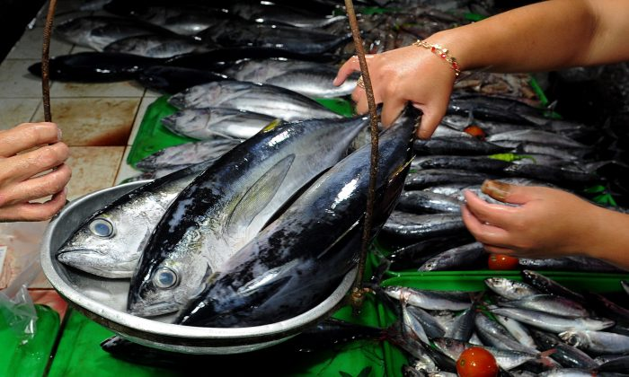 A vendor weighs yellowfin tuna at a market in Manila on October 2, 2015. (JAY DIRECTO/AFP/Getty Images)