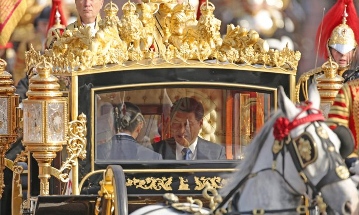Chinese Communist Party leader Xi Jinping and Queen Elizabeth II ride in the Diamond Jubilee State Coach along The Mall after a ceremonial welcome on his first state visit to the UK in London on Oct. 20, 2015. (Yui Mok/WPA Pool/Getty Images)