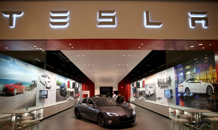 People look at a Tesla Motors vehicle on the showroom floor at the Dadeland Mall in Miami, FL., on Feb. 19, 2014. (Joe Raedle/Getty Images)