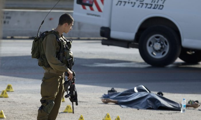Israeli soldiers stands by the body of a Palestinian man at the scene of a stabbing attack near the West Bank Jewish settlement of Adam, north of Jerusalem, Wednesday, Oct. 21, 2015. (AP Photo/Majdi Mohammed)
