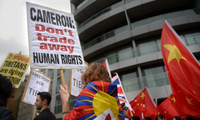 Demonstrators hold placards as Chinese President Xi Jinping and Prince Andrew, Duke of York visit Inmarsat on October 22nd, 2015 in London, England (Anthony Devlin - WPA Pool/Getty Images)