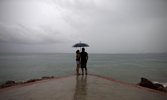 A couple looks out to sea as rainfall increases with the approach of Hurricane Patricia in Puerto Vallarta, Mexico, Friday, Oct. 23, 2015. (AP Photo/Rebecca Blackwell)