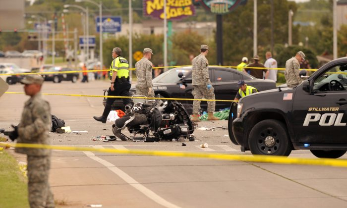 A damaged police motorcycle rests in the intersection after a vehicle crashed into a crowd of spectators during the Oklahoma State University homecoming parade, causing multiple injuries, in Stillwater, Oka., on Oct. 24, 2015. (AP Photo/Brody Schmidt)