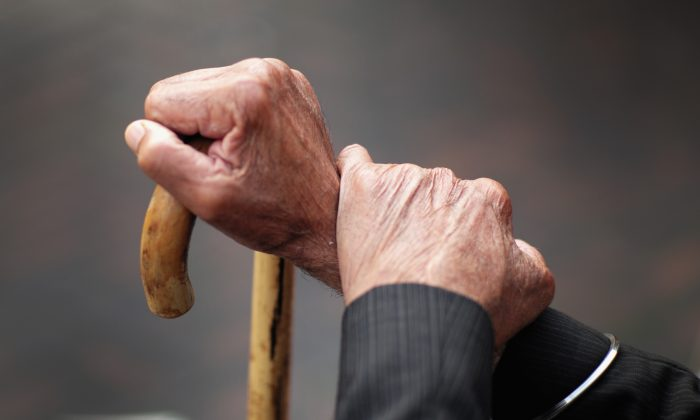 A pensioner holds his walking stick in this file photo. In America, Baby Boomers haven't saved enough to retire confortably and the next generations may well end up paying for it. (Christopher Furlong/Getty Images)