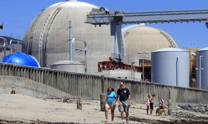 Beachgoers walk on the sand near the San Onofre nuclear power plant in San Clemente, Calif., on June 30, 2011. (AP Photo/Lenny Ignelzi)
