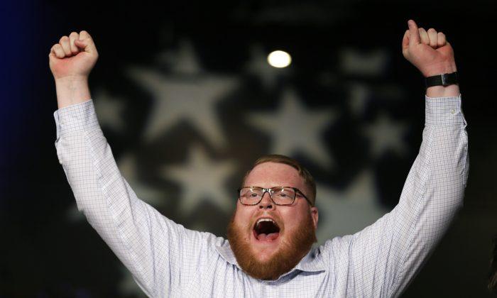 Reid Sheldahl, of Des Moines, Iowa, raises his arms as Democratic presidential candidate Sen. Bernie Sanders, I-Vt., speaks during the Iowa Democratic Party's Jefferson-Jackson fundraising dinner, Saturday, Oct. 24, 2015, in Des Moines, Iowa. (AP Photo/Charlie Neibergall)