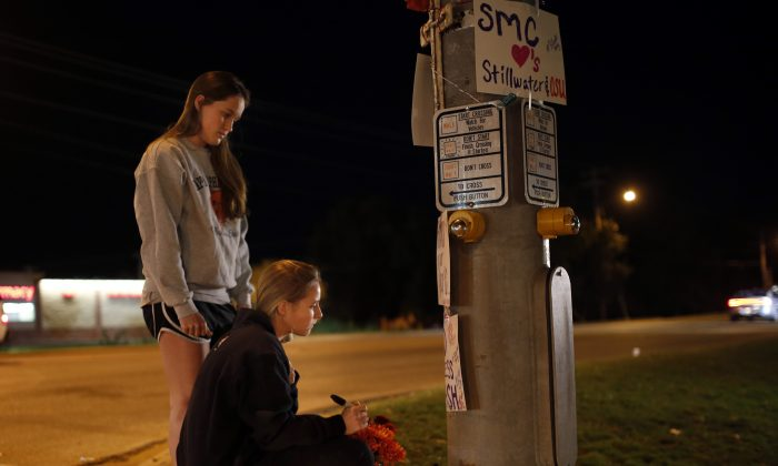 Oklahoma State students Kelly Cooke, right, and Rebecca Buchanan read messages on a memorial in Stillwater, Okla., Saturday, Oct. 24, 2015, near where a car crashed into spectators during the Oklahoma State University homecoming parade killing multiple and injuring several others. (Sarah Phipps/The Oklahoman via AP)