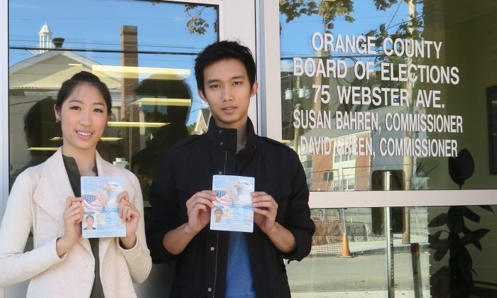 Ashley Wei and Andrew Fung stand outside the Board of Elections holding the U.S. the passports they used to demonstrate their citizenship. (Sue Jones)