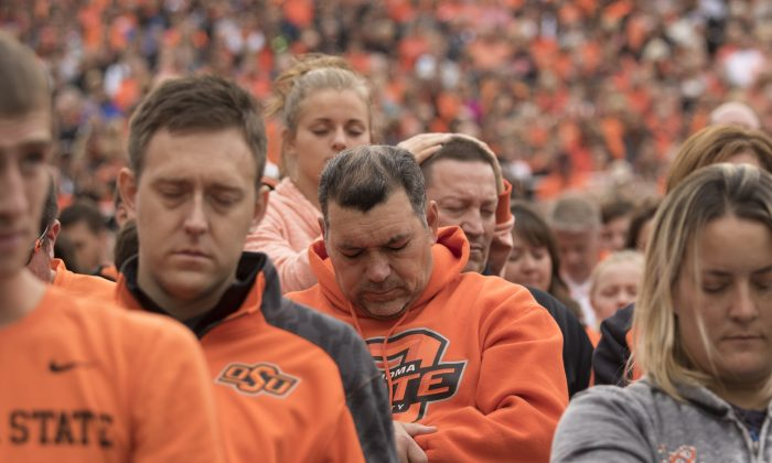 Oklahoma State football fans observe a moment of silence for the people killed by a car that crashed into the homecoming parade, during a NCAA college football game against the Kansas Jayhawks, at the Boone Pickens Stadium in Stillwater, Oklahoma, on Oct. 24, 2015. (J. Pat Carter/Getty Images)