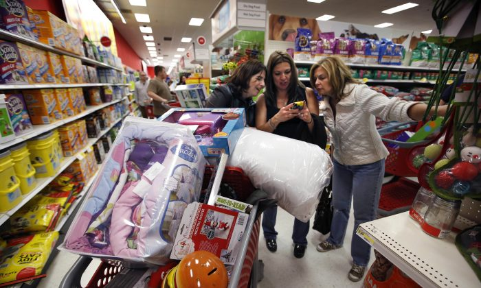 In this Nov. 28, 2014 file photo, Target shoppers Kelly Foley, left, Debbie Winslow, center, and Ann Rich use a smartphone to look at a competitor's prices while shopping shortly after midnight on Black Friday, in South Portland, Maine. Wal-Mart and Target, two of the biggest U.S. retailers, on Thursday, Oct. 29, 2015 rolled out plans to lure shoppers into stores during the holiday season by pushing discounts, free shipping and spiffed up stores. (AP Photo/Robert F. Bukaty, File)