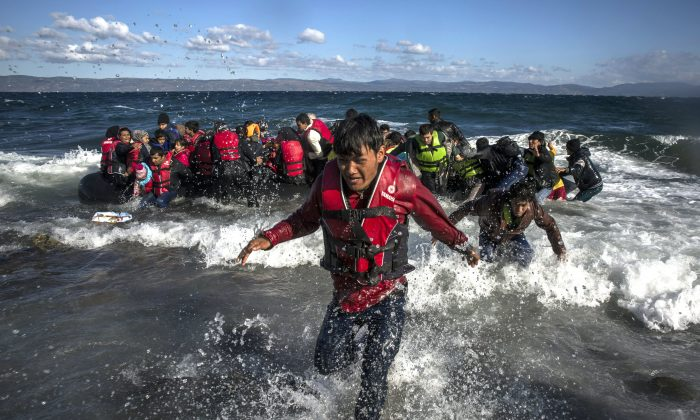 Afghan migrants disembark safely from their frail boat in bad weather on the Greek island of Lesbos after crossing the Aegean see from Turkey, Wednesday, Oct. 28, 2015. (AP Photo/Santi Palacios)