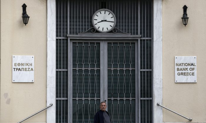A man stands in front of a National Bank branch in Piraeus, near Athens, Saturday, Oct. 31, 2015. Greece and its bailout creditors remain divided over how to toughen foreclosure laws, according European Union officials, though the overall talks on getting the country the next batch of loans are on track. (AP Photo/Yorgos Karahalis)